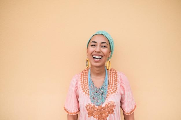 Jonge vrouw van gemengd ras die lacht op camera terwijl ze traditionele kleding draagt