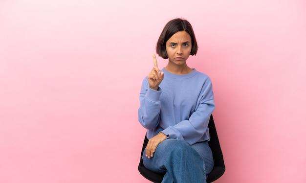 Jonge vrouw van gemengd ras die op een stoel zit en er een telt met serieuze uitdrukking