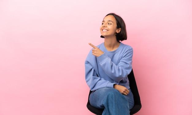 Jonge vrouw van gemengd ras die op een stoel zit en naar de zijkant wijst om een product te presenteren
