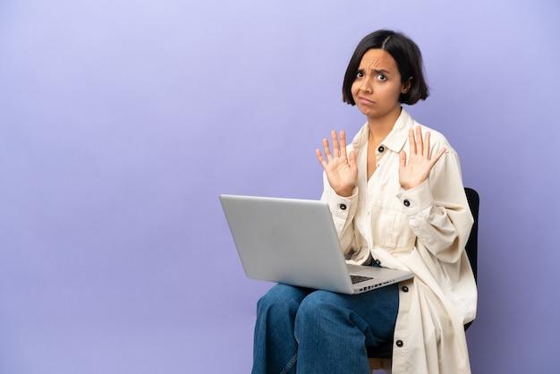 Jonge vrouw van gemengd ras die op een stoel zit met een laptop, isoleerde nerveuze handen naar voren uitrekkend