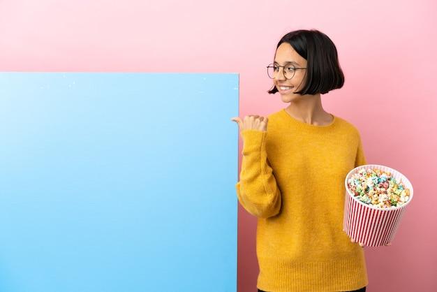 Jonge vrouw van gemengd ras die popcorn vasthoudt met een grote banner geïsoleerde achtergrond die naar de zijkant wijst om een product te presenteren