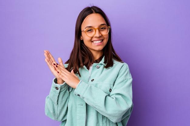 Jonge vrouw van gemengd ras die zich energiek en comfortabel voelt, zelfverzekerd handen wrijft.