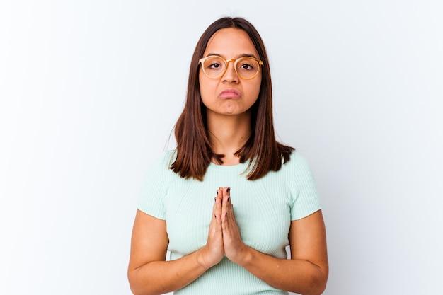 Jonge vrouw van gemengd ras geïsoleerd bidden, toewijding tonen, religieuze persoon op zoek naar goddelijke inspiratie.