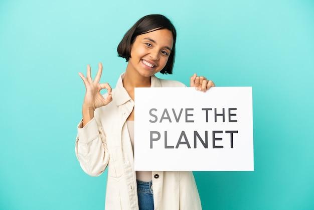 Jonge vrouw van gemengd ras geïsoleerd met een bordje met de tekst save the planet en een overwinning vieren