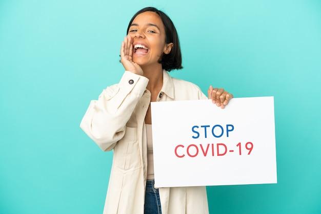 Jonge vrouw van gemengd ras geïsoleerd met een bordje met de tekst stop covid 19 en schreeuwen