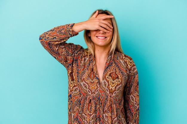 Jonge vrouw van gemengd ras geïsoleerd op blauw dekt ogen met handen, glimlacht in grote lijnen wachtend op een verrassing.