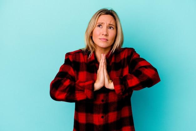 Jonge vrouw van gemengd ras geïsoleerd op blauw hand in hand bidden in de buurt van de mond, voelt zich zelfverzekerd.