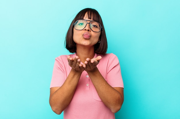 Jonge vrouw van gemengd ras geïsoleerd op blauwe achtergrond die lippen vouwt en handpalmen vasthoudt om luchtkus te sturen.