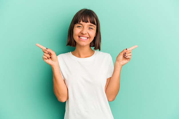 Jonge vrouw van gemengd ras geïsoleerd op blauwe achtergrond met nekpijn als gevolg van stress, masseren en aanraken met de hand.