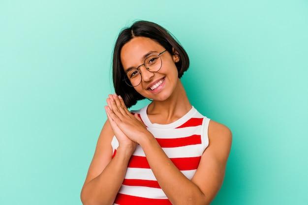 Jonge vrouw van gemengd ras geïsoleerd op blauwe achtergrond voelt zich energiek en comfortabel en wrijft zelfverzekerd over de handen.