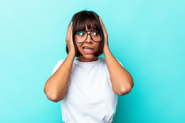 Jonge vrouw van gemengd ras geïsoleerd op een blauwe achtergrond die oren bedekt met handen die proberen niet te hard geluid te horen.