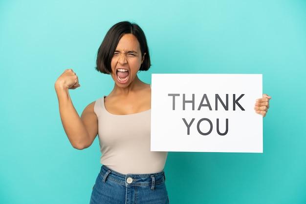 Jonge vrouw van gemengd ras geïsoleerd op een blauwe achtergrond met een bordje met de tekst dank u en een sterk gebaar doen