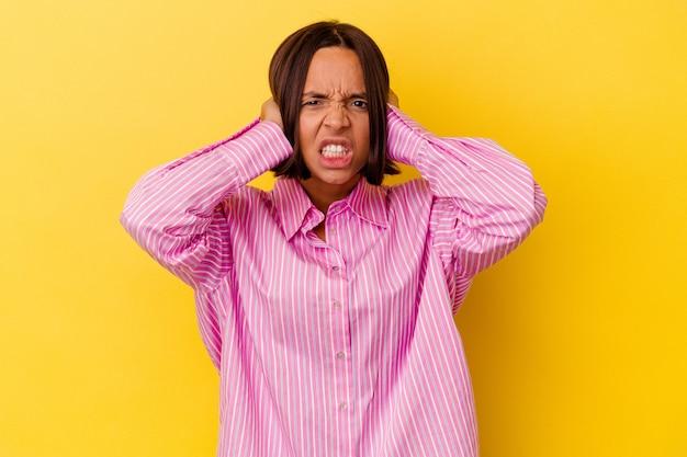 Jonge vrouw van gemengd ras geïsoleerd op een gele achtergrond die oren bedekt met handen die proberen niet te hard geluid te horen.