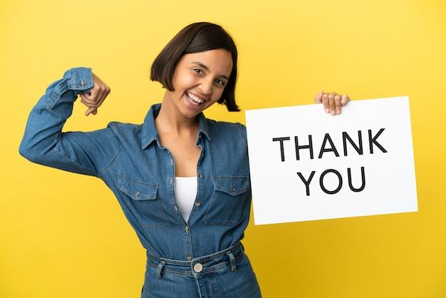 Jonge vrouw van gemengd ras geïsoleerd op een gele achtergrond met een bordje met de tekst dank u en een sterk gebaar
