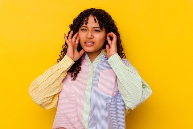 Jonge vrouw van gemengd ras geïsoleerd op gele bedekkende oren met vingers, gestrest en wanhopig door een luide ambient.