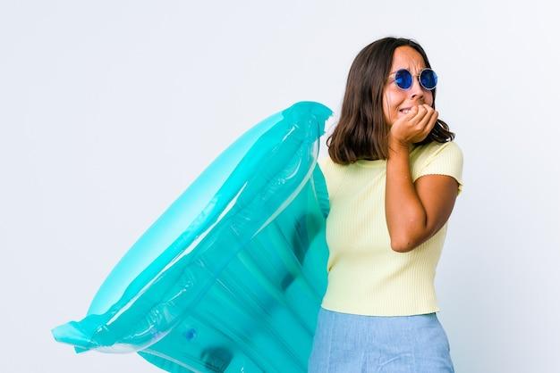Jonge vrouw van gemengd ras met een luchtbed dat vingernagels bijt, nerveus en erg angstig.