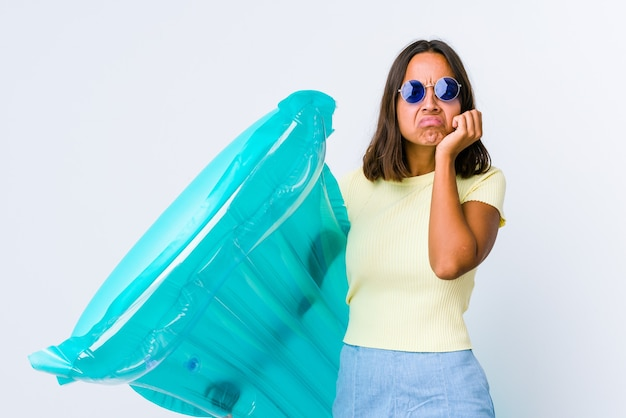 Jonge vrouw van gemengd ras met een luchtbed die zich verdrietig en peinzend voelt en naar kopieerruimte kijkt.