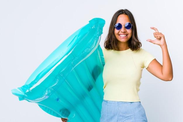 Jonge vrouw van gemengd ras met een luchtbed met iets kleins met wijsvingers, glimlachend en zelfverzekerd.