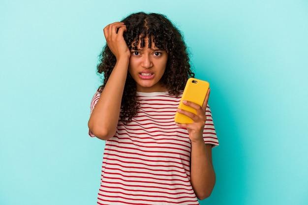 Jonge vrouw van gemengd ras met een mobiele telefoon geïsoleerd op een blauwe achtergrond die geschokt is, ze herinnert zich een belangrijke vergadering.
