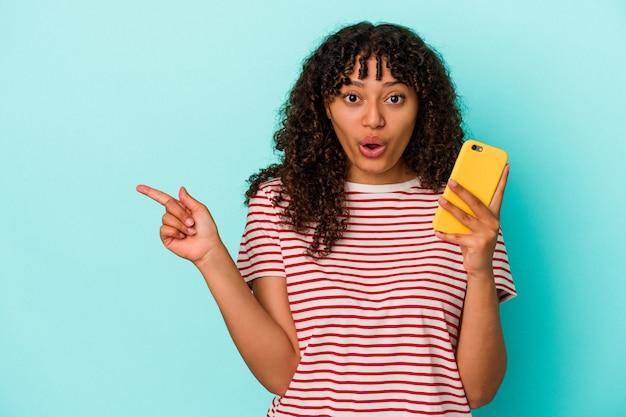 Jonge vrouw van gemengd ras met een mobiele telefoon geïsoleerd op een blauwe achtergrond die naar de zijkant wijst