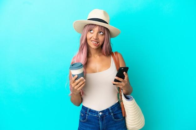 Jonge vrouw van gemengd ras met een strandtas met pamela geïsoleerd op een blauwe achtergrond met koffie om mee te nemen en een mobiel terwijl ze aan iets denkt