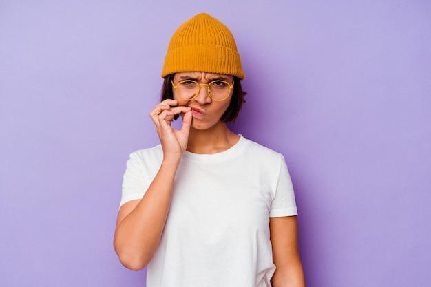 Jonge vrouw van gemengd ras met een wollen muts geïsoleerd op een paarse achtergrond met vingers op de lippen die een geheim bewaren.
