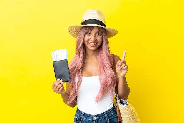 Jonge vrouw van gemengd ras met paspoort en strandtas geïsoleerd op een gele achtergrond die een geweldig idee benadrukt