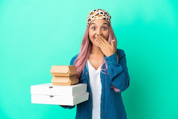 Jonge vrouw van gemengd ras met pizza's en hamburgers geïsoleerd op een groene achtergrond, blij en glimlachend die de mond bedekt met de hand