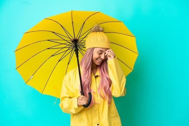 Jonge vrouw van gemengd ras met regenbestendige jas en paraplu lachend