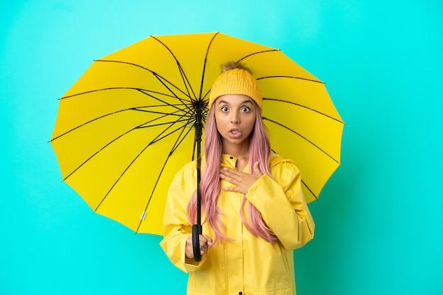 Jonge vrouw van gemengd ras met regenbestendige jas en paraplu verrast en geschokt terwijl ze naar rechts keek