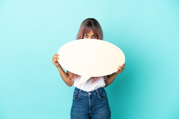 Jonge vrouw van gemengd ras met roze haar geïsoleerd op blauwe achtergrond met een lege tekstballon die erachter verstopt zit