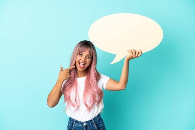 Jonge vrouw van gemengd ras met roze haar geïsoleerd op een blauwe achtergrond die een lege tekstballon vasthoudt en erop wijst