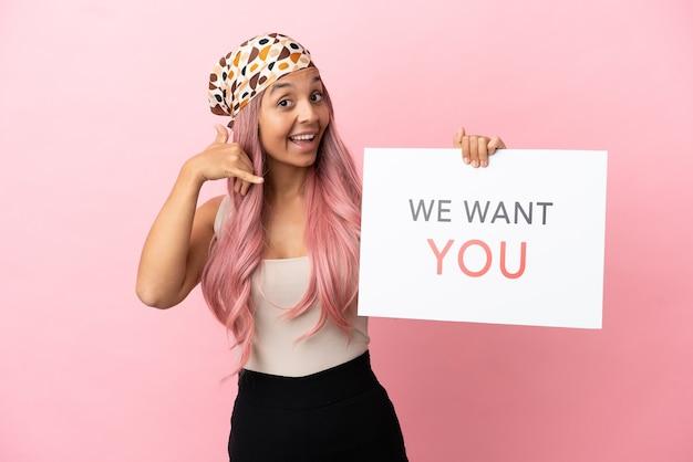 Jonge vrouw van gemengd ras met roze haar geïsoleerd op een roze achtergrond die we want you aan boord houdt en een telefoongebaar maakt