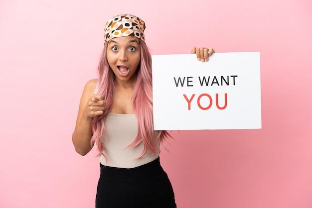 Jonge vrouw van gemengd ras met roze haar geïsoleerd op een roze achtergrond die we want you aan boord houdt en naar voren wijst