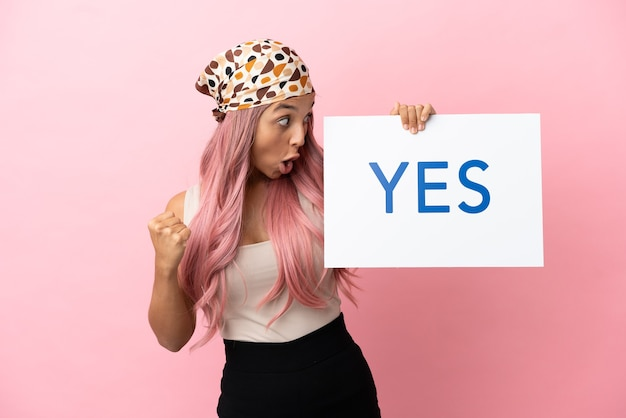 Jonge vrouw van gemengd ras met roze haar geïsoleerd op roze achtergrond met een bordje met de tekst ja en viert een overwinning