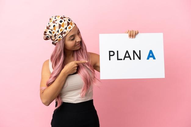 Jonge vrouw van gemengd ras met roze haar geïsoleerd op roze achtergrond met een bordje met het bericht plan a en erop wijzend