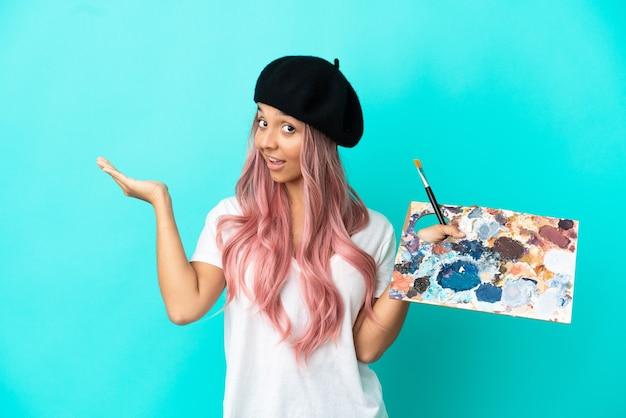 Jonge vrouw van gemengd ras met roze haar met een palet geïsoleerd op een blauwe achtergrond die de handen naar de zijkant uitstrekt om uit te nodigen om te komen