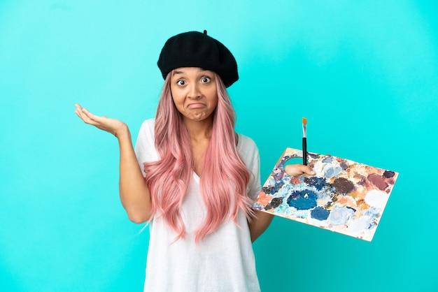 Jonge vrouw van gemengd ras met roze haar met een palet geïsoleerd op een blauwe achtergrond die twijfelt terwijl ze de handen opsteekt