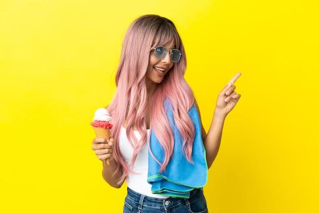Jonge vrouw van gemengd ras met roze haar met ijs geïsoleerd op een gele achtergrond die een geweldig idee benadrukt