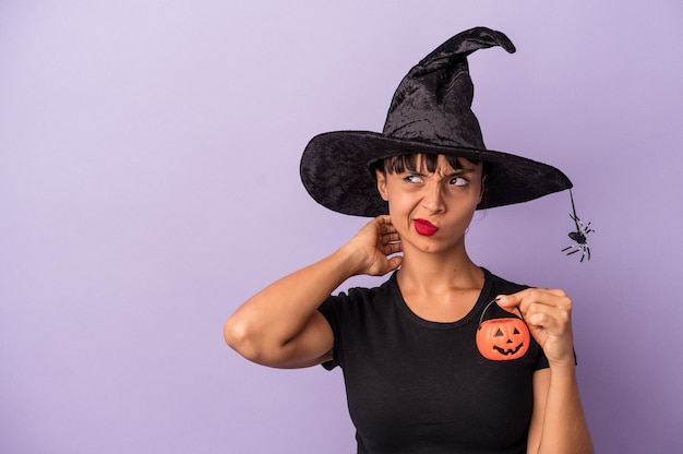 Jonge vrouw van gemengd ras vermomd als een heks geïsoleerd op een paarse achtergrond die de achterkant van het hoofd aanraakt, denkt en een keuze maakt.