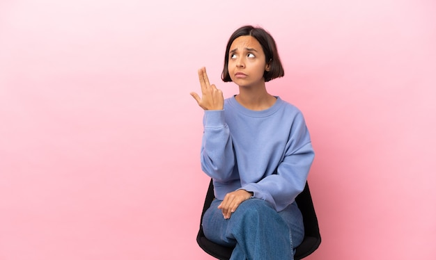 Jonge vrouw van gemengd ras zittend op een stoel geïsoleerd op een roze achtergrond met problemen bij het maken van zelfmoordgebaar