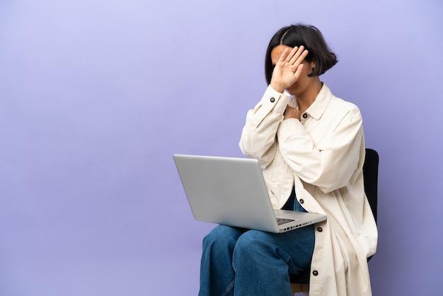 Jonge vrouw van gemengd ras zittend op een stoel met laptop geïsoleerd op een paarse achtergrond nerveuze handen naar voren uitrekkend