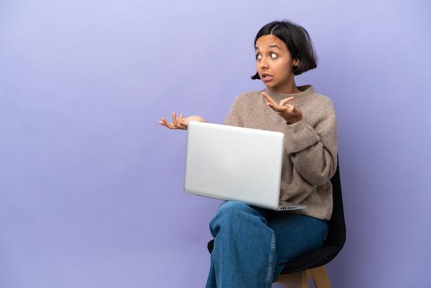 Jonge vrouw van gemengd ras zittend op een stoel met laptop geïsoleerd op paarse achtergrond met verrassingsuitdrukking terwijl ze opzij kijkt