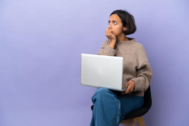 Jonge vrouw van gemengd ras zittend op een stoel met laptop geïsoleerd op paarse achtergrond nerveus en bang om de handen in de mond te leggen