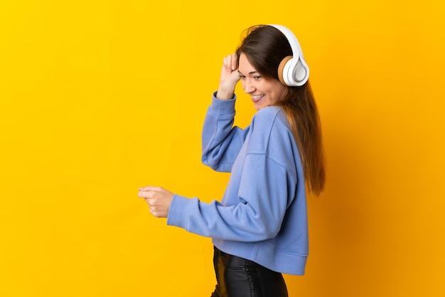 Jonge vrouw van ierland geïsoleerd op gele achtergrond muziek luisteren en dansen