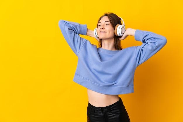 Jonge vrouw van ierland geïsoleerd op gele achtergrond muziek luisteren