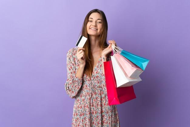 Jonge vrouw van ierland geïsoleerd op paarse muur met boodschappentassen en een creditcard en denken