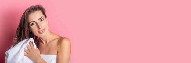 Jonge vrouw veegt haar natte haren af met een handdoek op een roze achtergrond.