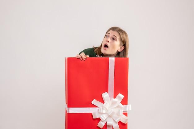 Jonge vrouw verbergen in huidige doos op wit