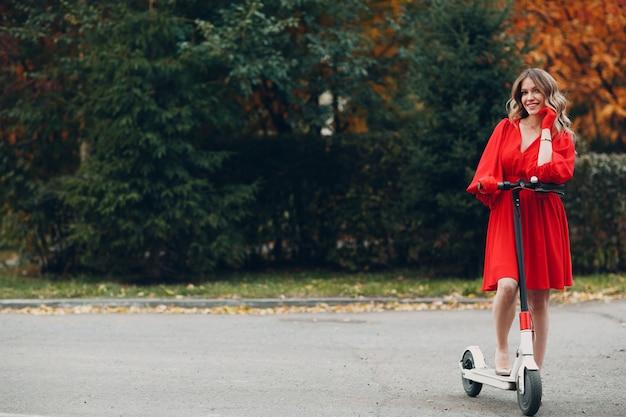 Jonge vrouw verblijft met elektrische scooter in rode jurk in het herfst stadspark